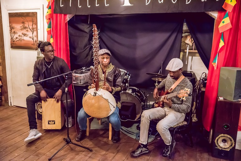 Senegalese musicians at an intimate dinner in London, middle performer plays the kora