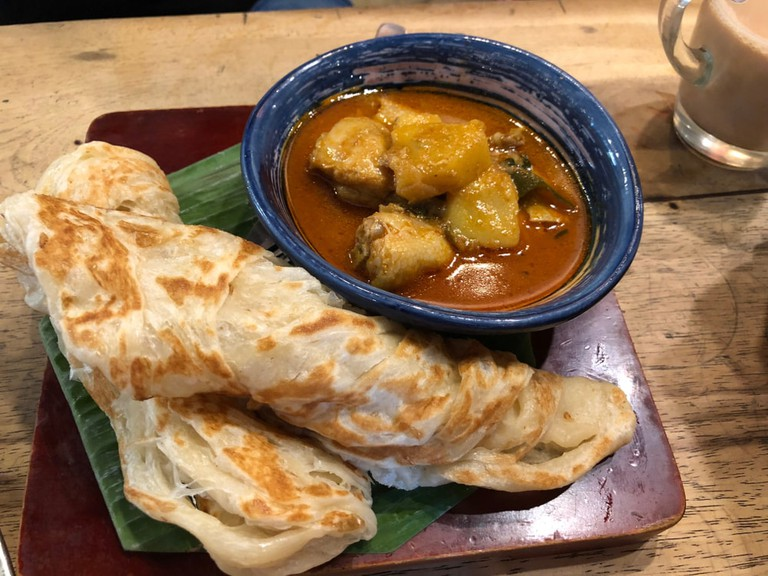 Roti Canai or Roti Prata Served With Curry Chicken as Dipping