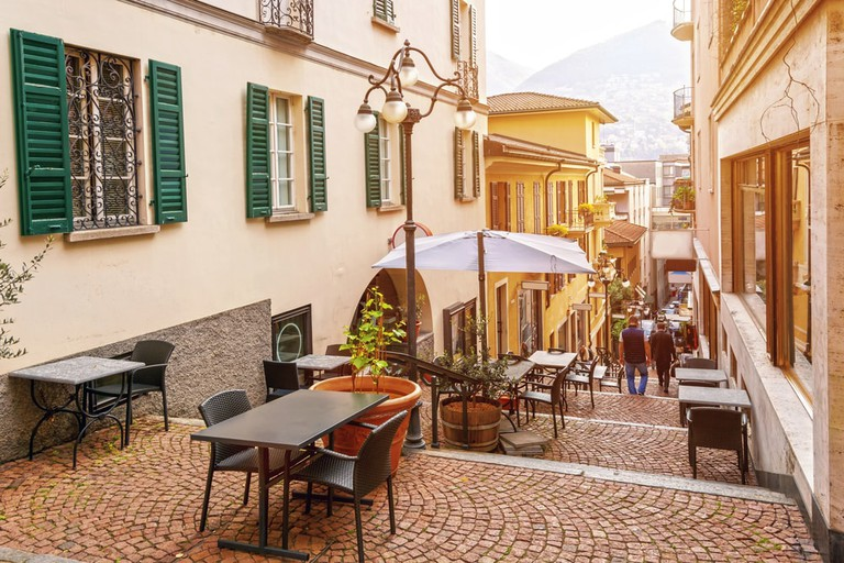 Narrow street with cafés and restaurants in the old town of Lugano, Switzerland
