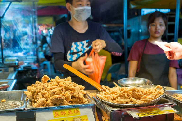 Night market vendor packing battered fried Fish 'n Chips and cuttlefish for buyer at Kuala Lumpur, Malaysia