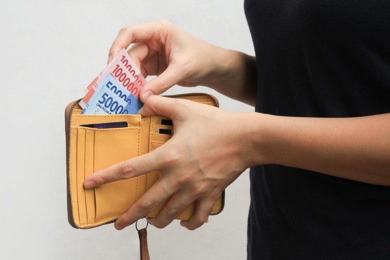 Hand open wallet and showing rupiah money