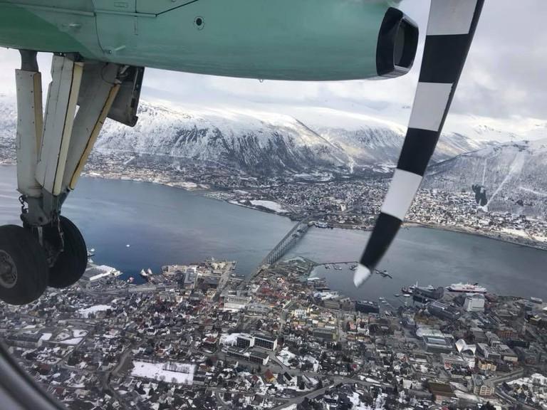 A Widerøe plane flying over Tromsø