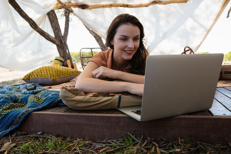 Young woman using laptop in tent