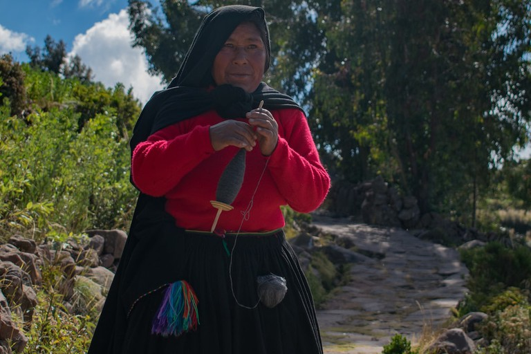 A woman walks along Taquile's cobblestoned streets whilst she spins the wool for her husband to knit with