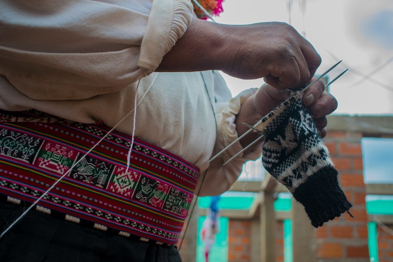 A Taquileño man wearing a calendar chupi (waistband) woven by the local women