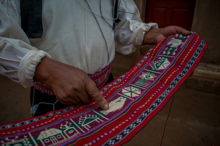 A local shows us a calendar waistband—depicting a prosperous harvest and a happy family home—woven by his former wife