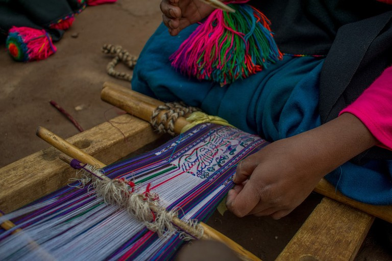 A woman spends months weaving the intricatechumpi waistband—many of which describe traditions and important festivities—using the oldest type of loom in the world
