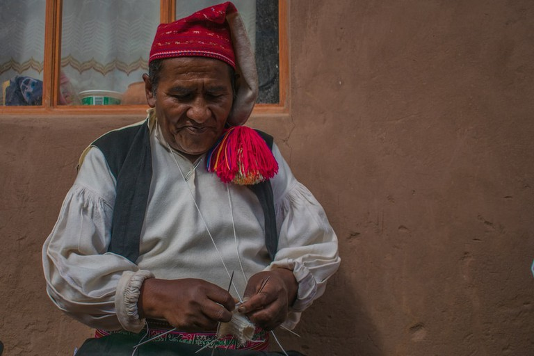 62-year-old Justino's wife recently died, so he now wears a red hat to the left side, indicating he is no longer married and is in mourning