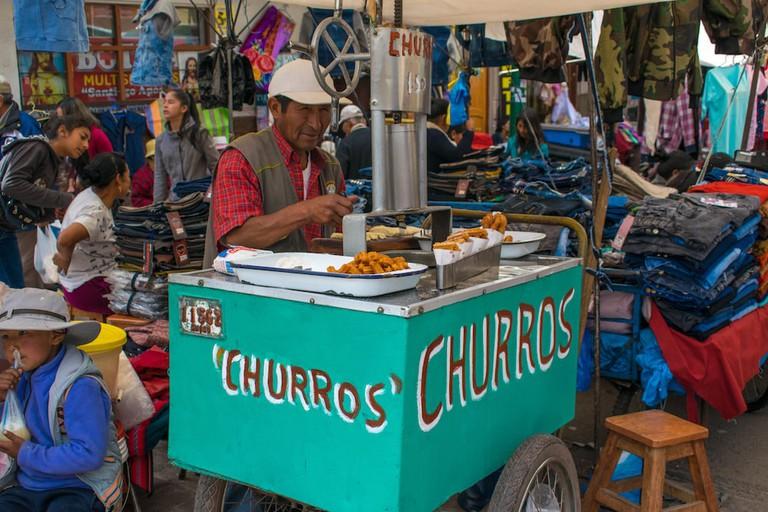 A man selling freshly made churros at Cusco's Barratillo market