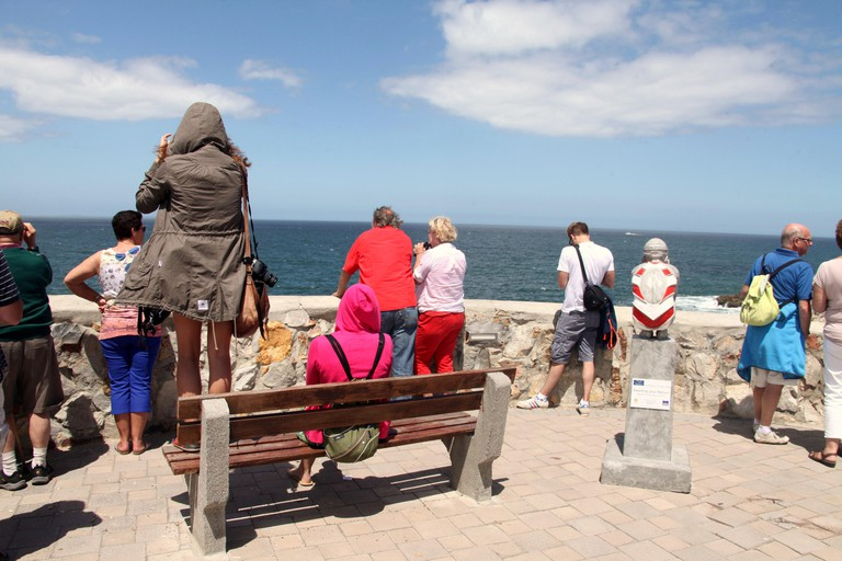 Tourists at Hermanus in South Africa watching southern right whales in the sea