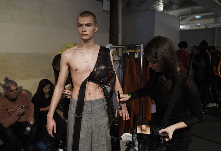 A model gets groomed backstage before the show by Ximon Lee during the London Men's Fashion Week