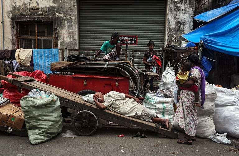 An Indian man taking a nap surrounded by waste sacks in the streets of Mumbai