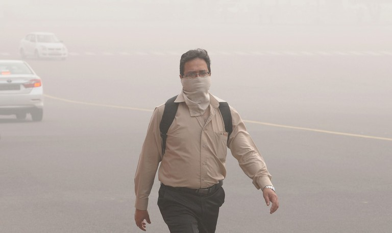 An Indian man with his face covered walks at Rajpath Avenue in Delhi as the city struggles with heavily polluted air