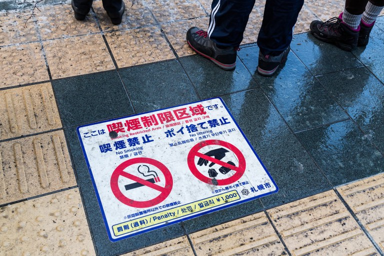 Warning and penalty signage on the street in Sapporo, Japan
