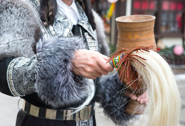 Yakut traditional dancer holding the white horse's tale decorated with colorful beads and the wooden goblet