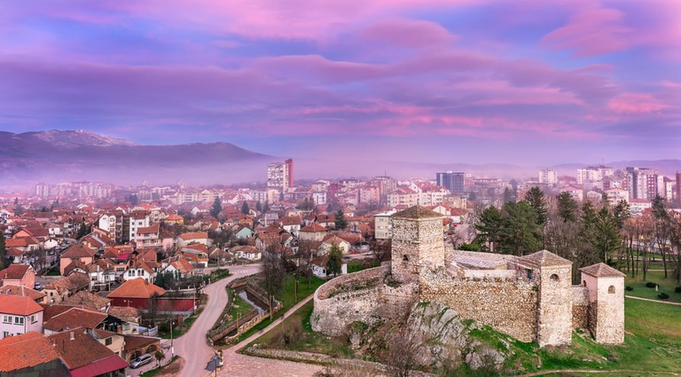 Colorful, magenta, sunset sky over misty cityscape panorama and foreground ancient fortress in Pirot, Serbia