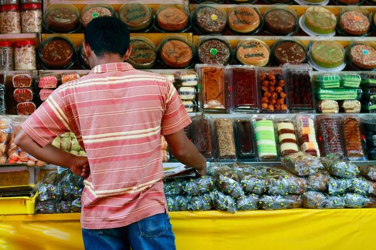 A customer is buying cakes at Chow Kit Market in Kuala Lumpur