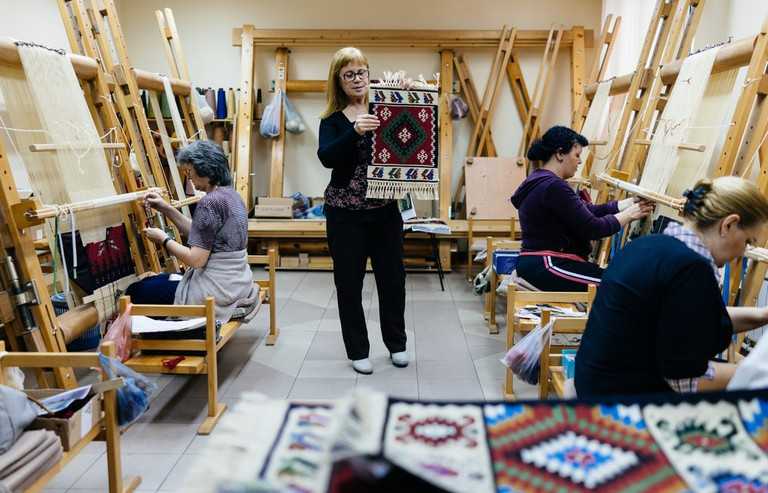Woman presenting carpets in aa workroom in Pirot, Serbia