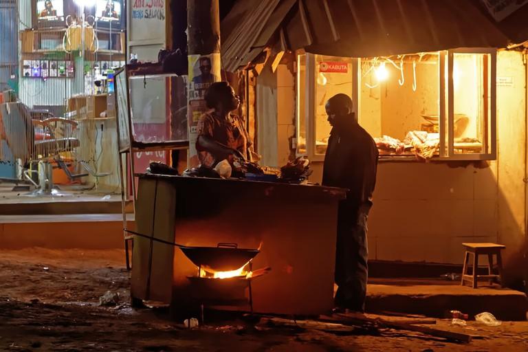 A street vendor prepares food in Wakiso District, Uganda