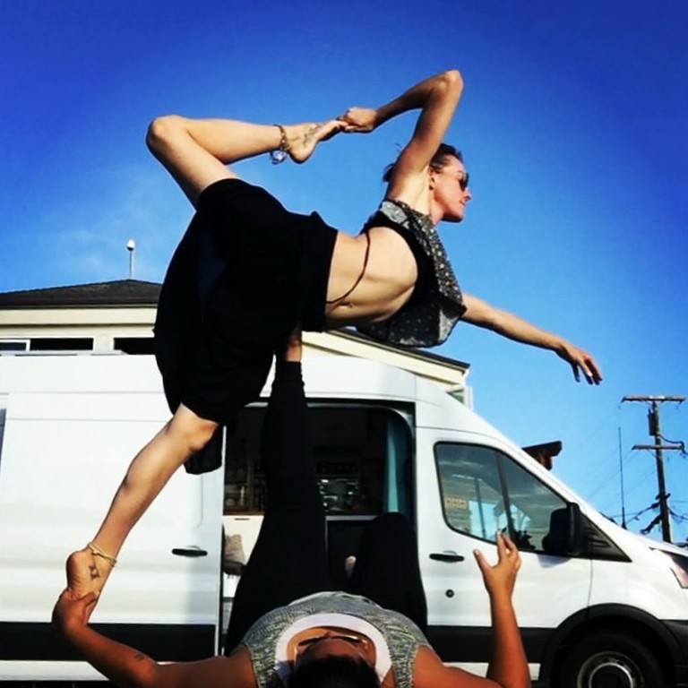 Lacey Mayer and Breanne Acio practice yoga outside of their van