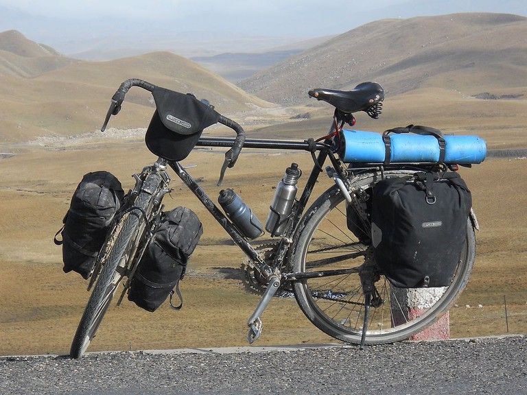 A loaded touring bicycle, with drop bars, 700c wheels, racks panniers and bar bag.