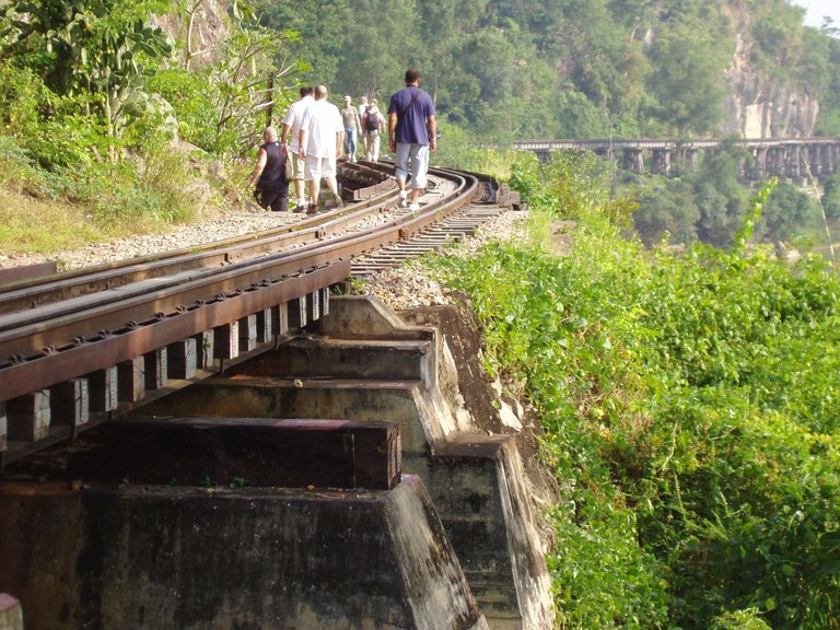 Tourists walking along a stretch of track on the Death Railway