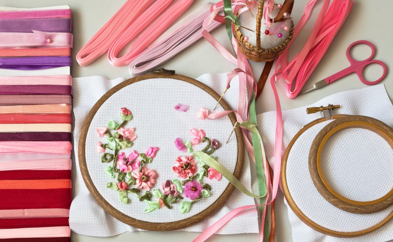 Embroidery process with satin ribbons of spring flowers and an accessories for needlework