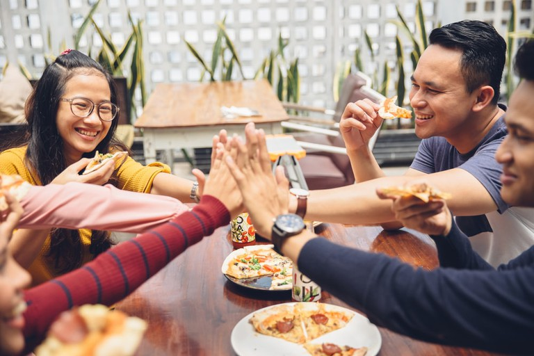 Malaysian friends spending time together over pizza