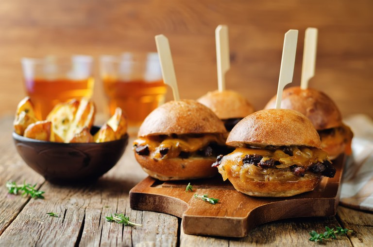 French Onion beef sliders with beer on a wood background