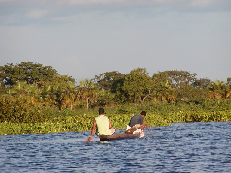 Fishermen in a typical wooden canoe in the Magdalena River