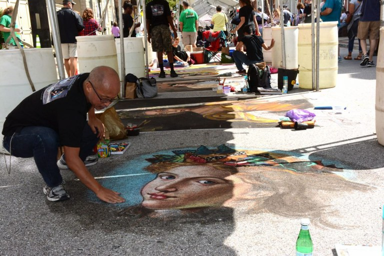 "Tomateru ""ToMo"" Saito creates a chalk portrait for the 2017 Madonnari Arts Festival."
