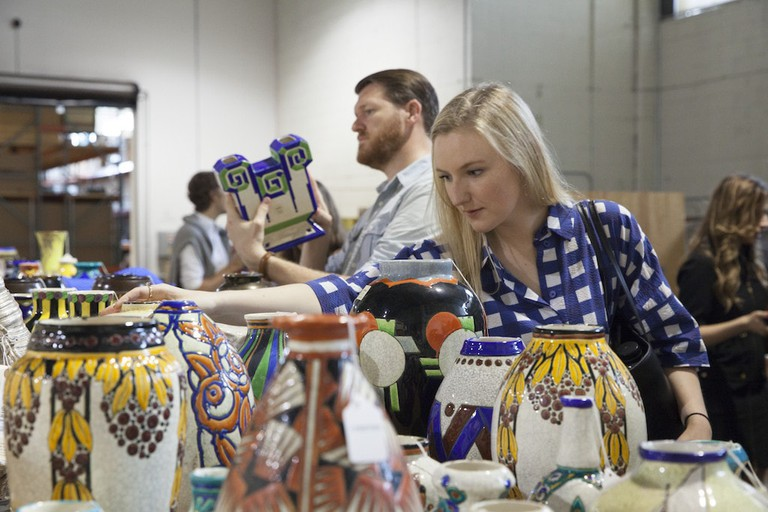 Guests inspect ceramic pots on view at Redstone warehouse