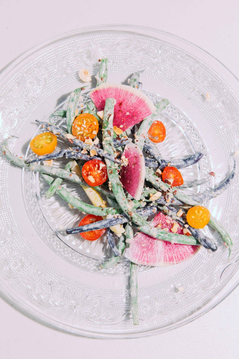 Multi-colored haricot verts salad with house-fermented THCA creme fraiche with heirloom tomato and hazelnuts