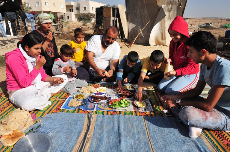 A Bedouin family enjoy an array of traditional salads and barbequed freshly cut meat from a slaughtered lamb for the holiday of Eid al-Adha