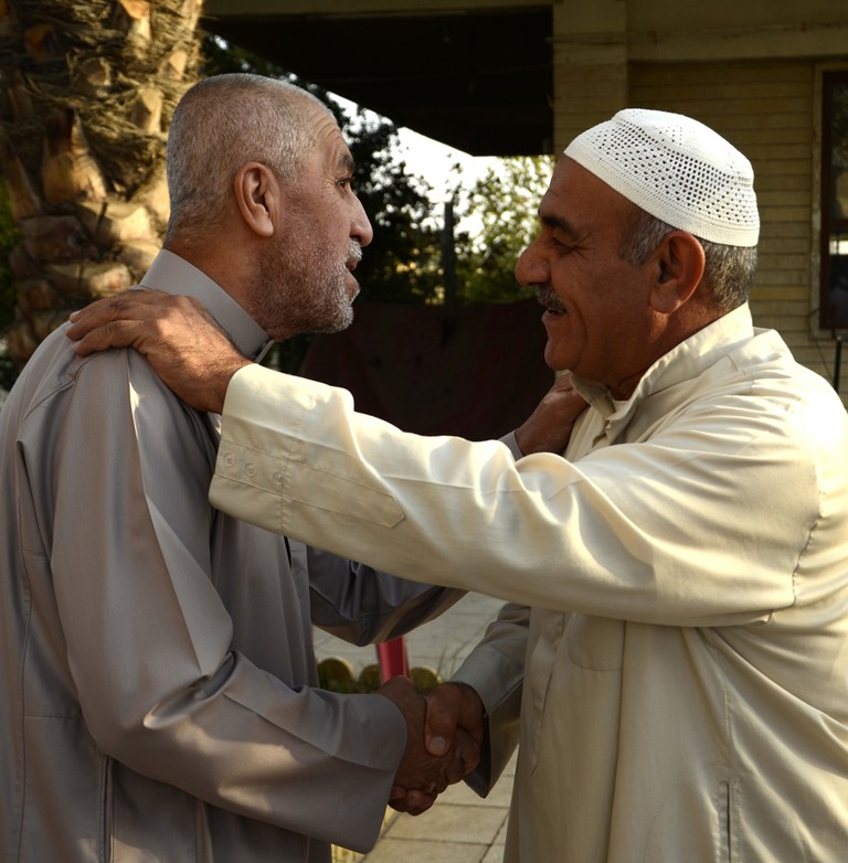 Iraqi Sunni men greet each other after Eid al-Adha prayers in Mosul city