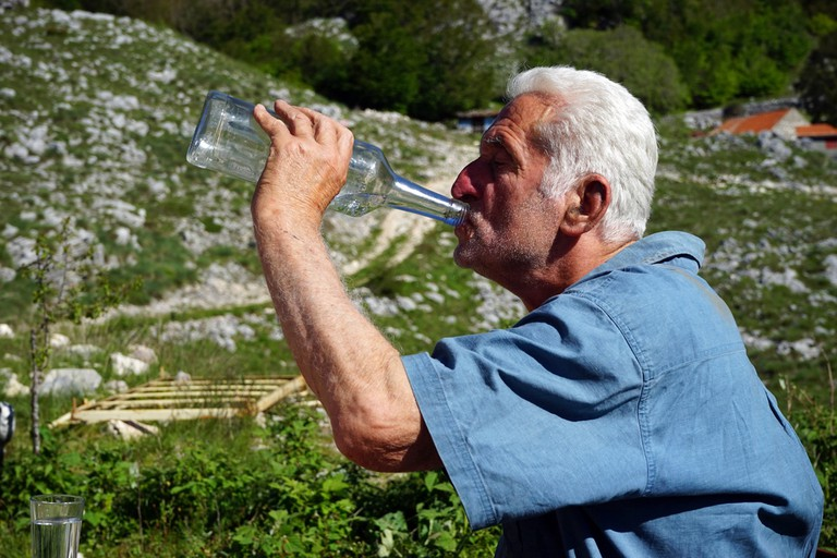 Man drinking out of a glass bottle in Montenegro