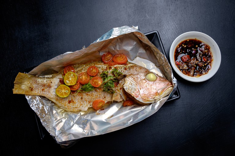 Baked fish with tomatoes, herbs and spices