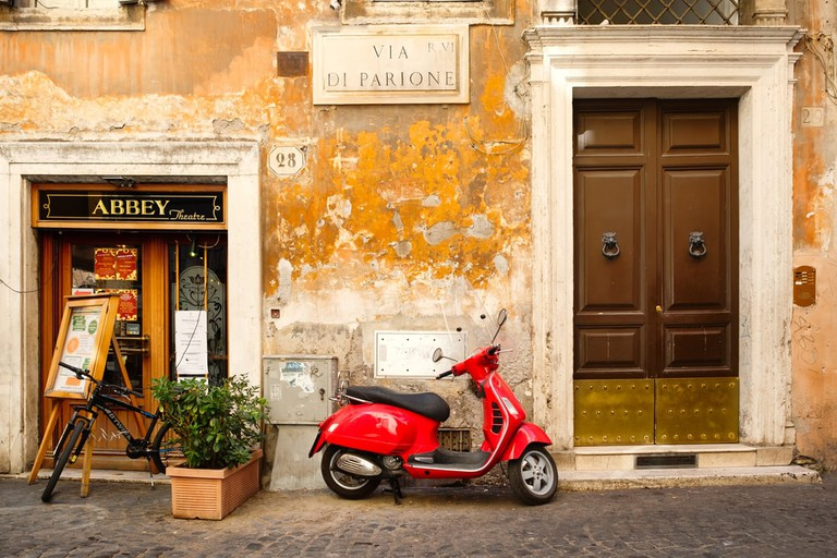 Red vesper on a narrow cobblestoned street in Rome, Italy.