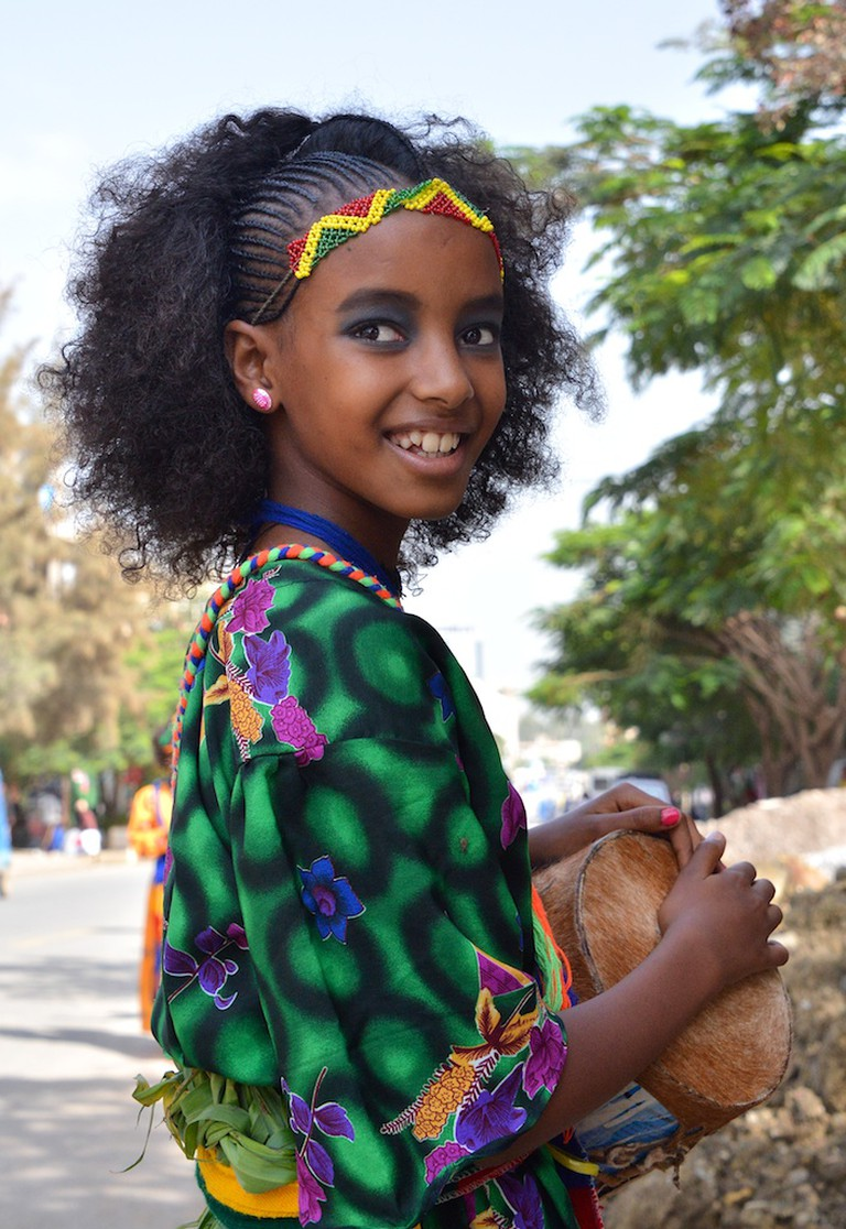 An Ethiopian girl holds her drum, ready to perform a traditional song