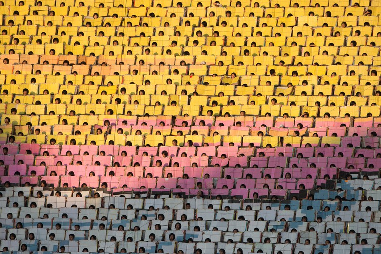Participants hold sheets of coloured material as they wait to perform during an 'Arrirang Festival mass games display'