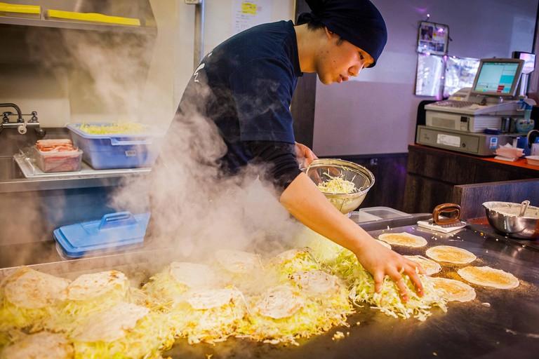 Chef Cooking Okonomiyaki, in a restaurant of Okonomi-mura, Hiroshima, Japan.