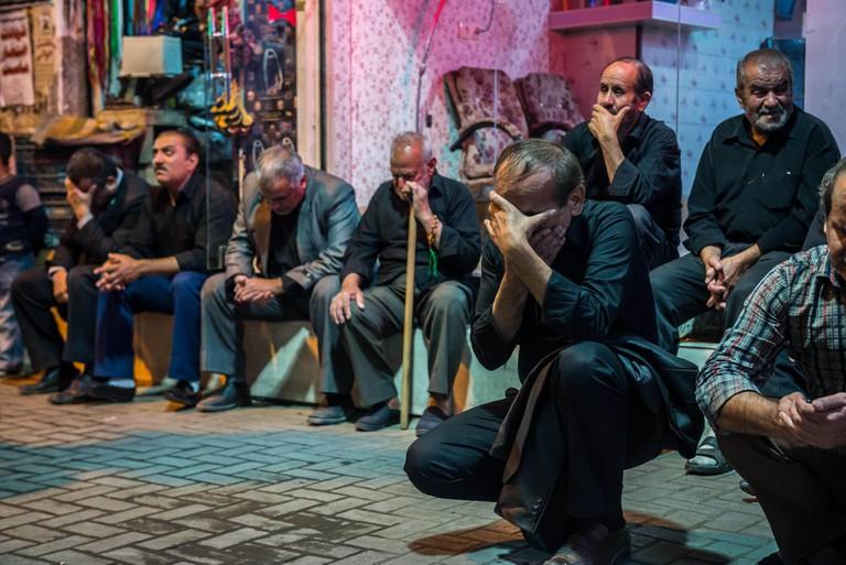 Man praying and singing to honour Husayn ibn Ali
