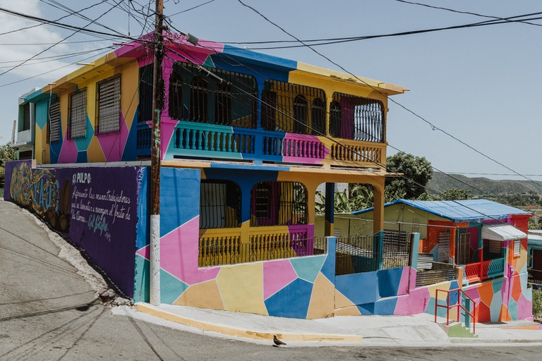 Project Yaucromatic in Yauco, PR, promotes public art against the invisibility of the island—made possible by Puerto Rican artists and muralists. On the right, a house with a blue FEMA tarp as a roof, almost 1 year after Hurricane Maria.