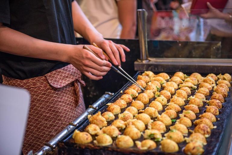 Takoyaki being prepared at a foodstall in Osaka, Japan.