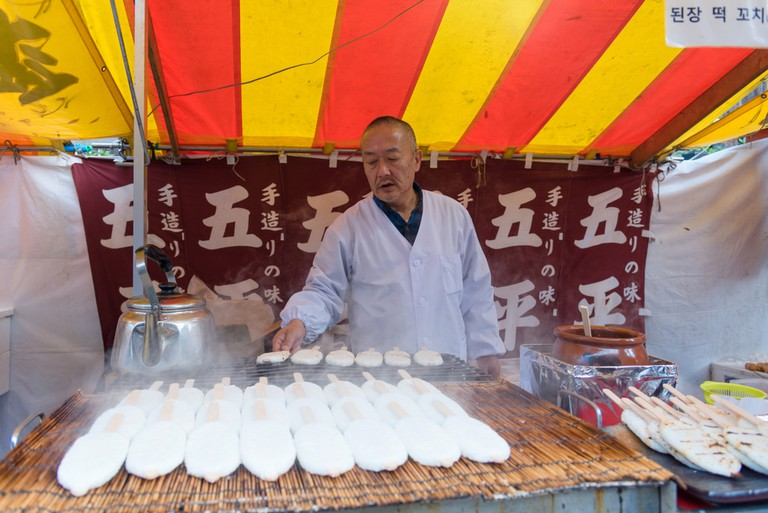 Japanese man selling goheimochi rice cake at shop on the street
