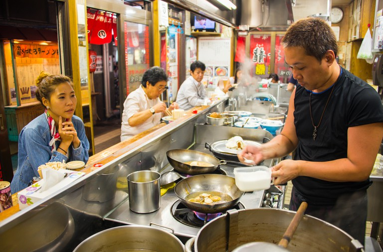 A man cooks ramen to serve to his customers in Sapporo, Japan.