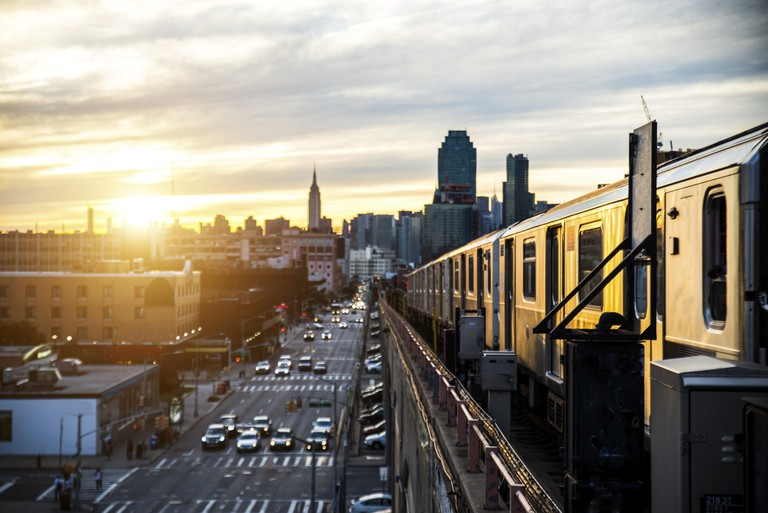 Subway train in New York at sunset and Manhattan cityscape view.