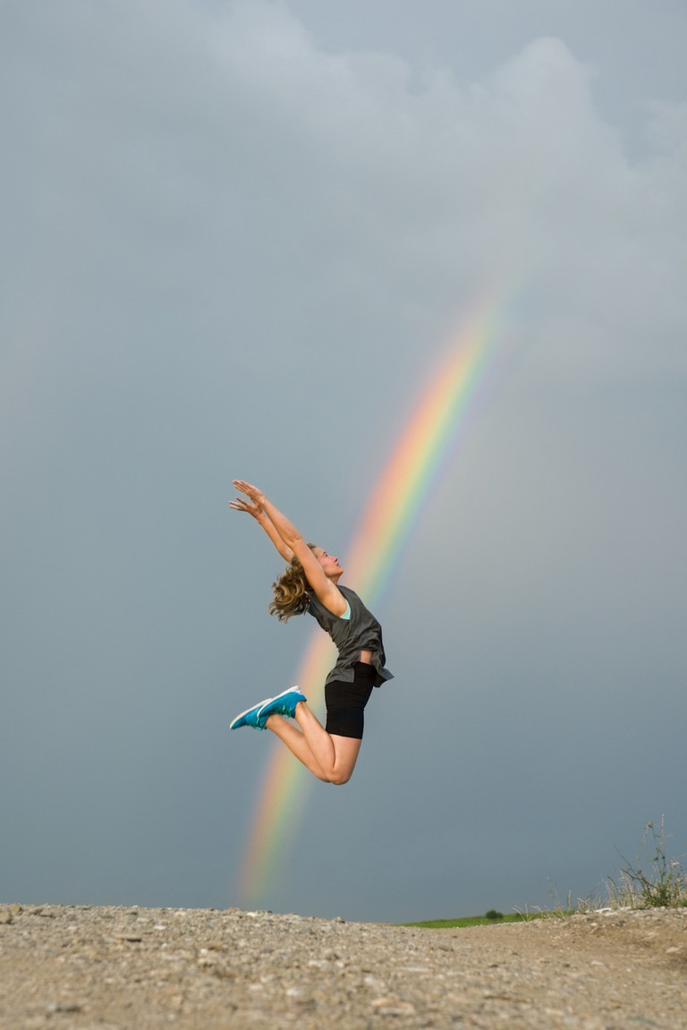 Woman Jumping In Front Of The Rainbow On Grey Sky