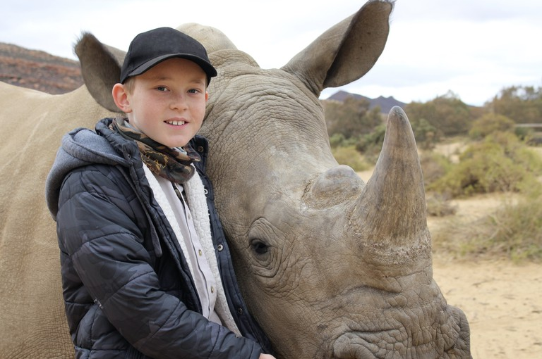 Hunter Mitchell with an adult rhino
