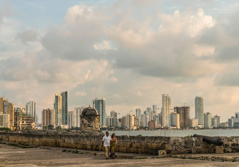 """A middle-aged couple walking atop the stone wall of the Ciudad Vieja or """"Old City"""" of Cartagena, Colombia.  The  old colonial ci"""